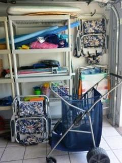 Garage fully stock with beach chairs, toys, boogie boards, and beach cart
