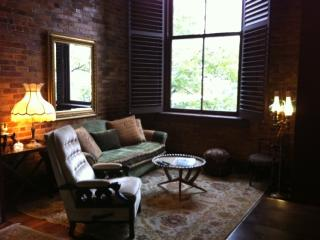Living room with exposed brick, high celings with beams and 10 ft orig windown overlooking downtown