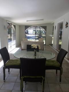Fully screened entertaining area with lounge and dining table separated with double bi fold doors