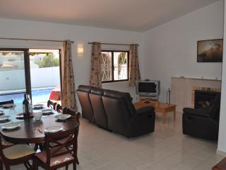Lounge with large dining table, large sofas, log fire, tv with English channels, patio doors to pool