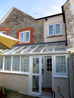 Conservatory has washing machine, storage space, backs to kitchen and patio