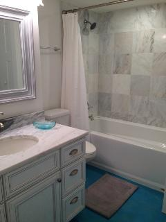All new guest bath with extra deep tub and marble surround.