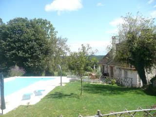 Pool, terrace and house, with countryside views beyond