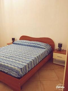 Camera da letto con comodini, comò, specchiera ed ampio armadio.