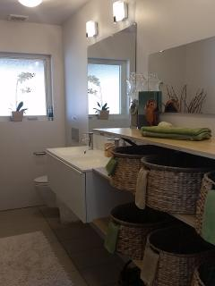 main bath has double wall hung sink and toilet with three large shelves and six baskets for guests toiletry bags and...