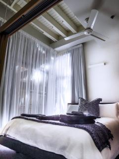 Bedroom with exposed beams, lots of soft light, ceiling fan and airconditioning