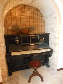 The grandma's piano from the early 20th century under an arch in the dining room