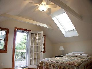 Master bedroom upstairs with ceiling fan and door to roof deck