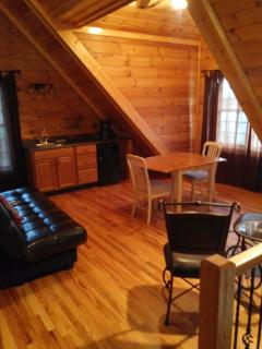 loft with futon, game table, sink & fridge, & windows