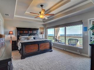 Master Bedroom with private covered balcony, large King size bed, Flat screen TV, and DVD player.