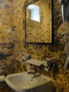 particolare bagno scavato nella roccia e vecchi specchi in ferro battutto