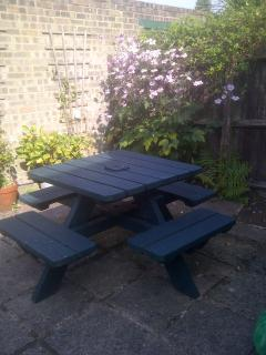 Enclosed paved garden.  Bench and picnic table with umbrella.  Garage and parking at back.