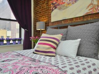 Detail of bed against original exposed brick wall
