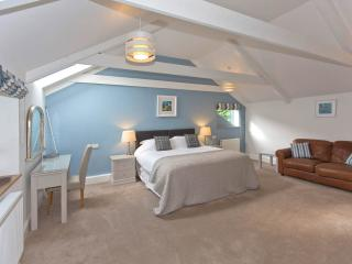 Large master bedroom with super king bed, seating area and ensuite shower room.