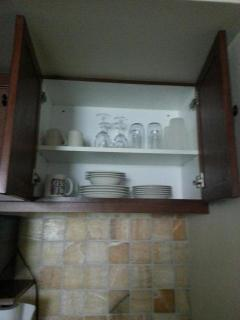 Kitchenette's cabinet is fully stocked with plates, glasses and coffee cups