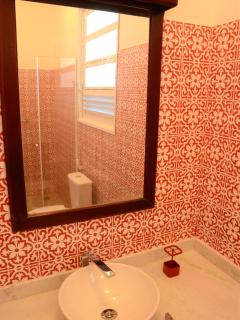 The main bathroom has a marble counter and walk-in tile shower.