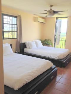 Master bedroom w. 2 queen beds, ensuite bathroom,air conditioning,fan,walk-in,balcony,Ocean View!!