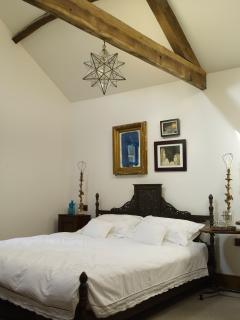 The super king-size bed sits centre stage in this light and airy master bedroom.