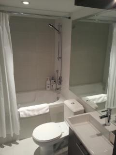 Sparkling clean bathroom with tub and shower combination.