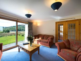 Stob Binnein living area with sliding patio doors opening onto a patio with garden furniture