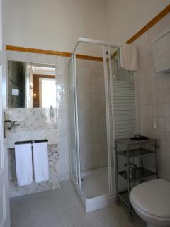 private bathroom in stone with shower + divan sink, toilet, trash, towels,hairdryer, shampoo and gel
