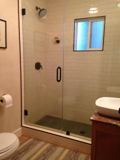 Glass enclosed shower with ceramic tile
