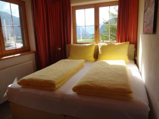 Cosy bedroom in traditional, tyrolian farmhouse style with great views over the valley (bedroom 2).