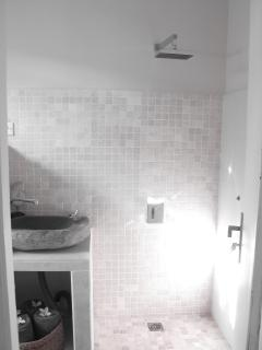 Bathroom with marble wall shower, water heater, toilet