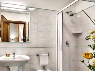 Leading from the living room is the bathroom, decorated with clean, crisp white tiles.