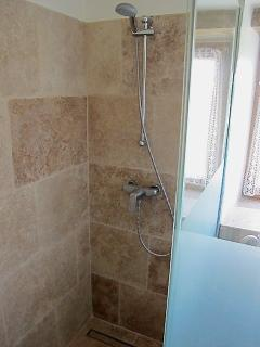 detail of spacious walk in, stone-lined shower, ground floor bathroom