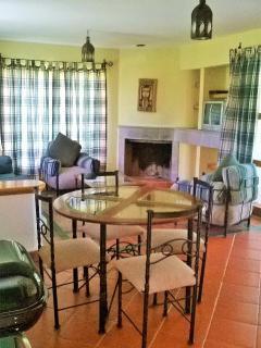 estancia con comedor, sala con sofa cama, tv y chimenea