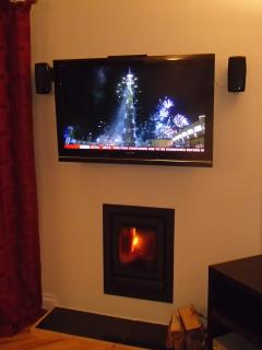 Wood burning stove with wide screen TV above