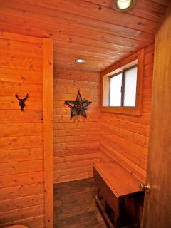 Bathroom on upper level with knotty pine walls and ceiling