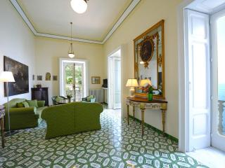 spacious living room furnished with ancient furniture and balconies facing the sea and Amalfi
