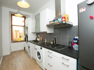 Well equipped modern white gloss kitchen, with clothes washer and clothes dryer.