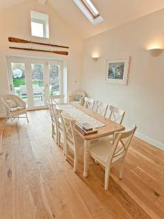 The sun room with access to the garden is ideal for alternative dining-bright and airy