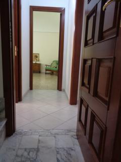 Zona ingresso. Di fronte camera con zona soggiorno, a sinistra cucina, a destra corridoio.