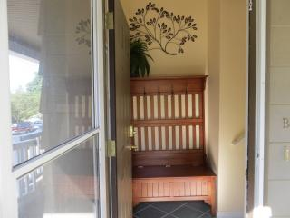 Walking through the door you will find an entryway with coat hooks, a storage bench, and umbrellas.