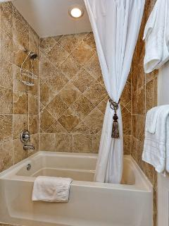 Large inviting shower with soaking tub.