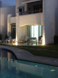 Night time view of the pool and patio with subtle lighting