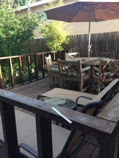 Table, chairs, loungers and umbrella in backyard