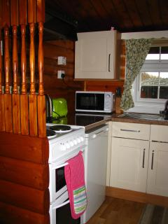 Kitchen with cooker, kettle, toaster, microwave, fridge with small integrated freezer section