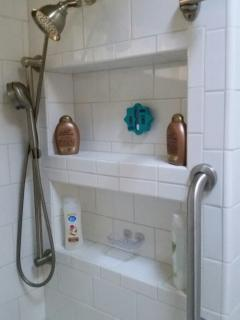 Shower with an assortment of soaps and hair care products. 4 sets of towels.