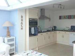 large kitchen area with dishwasher, microwave, hob, grill and oven