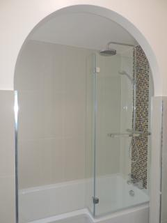 Large bath with rain head shower