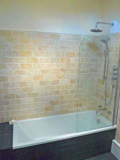 Natural stone and underfloor heating add a touch of luxury to the downstairs bathroom