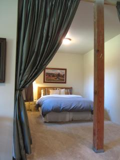 Lower level queen bed with privacy curtains