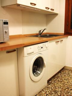 The washing machine is in the kitchen as well.