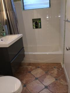 bathroom with tiled floors and lighted mirror...modern yet warm