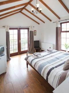 Master bedroom with solid oak flooring, vaulted ceiling, ensuite & Juliet balcony to rear
